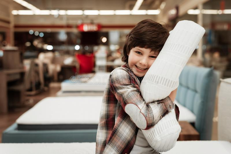 Joyful boy enjoying softness of orthopedic pillow rejoices in furniture store. Joyful little boy hugs orthopedic pillow sitting on mattress royalty free stock photography