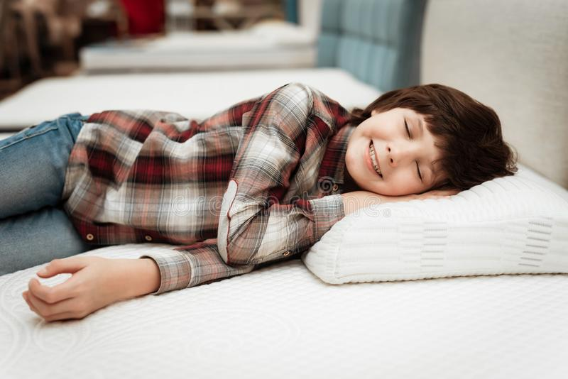 Joyful boy enjoying softness of orthopedic pillow rejoices in furniture store. Joyful little boy lies on orthopedic pillow in mattress store royalty free stock photography