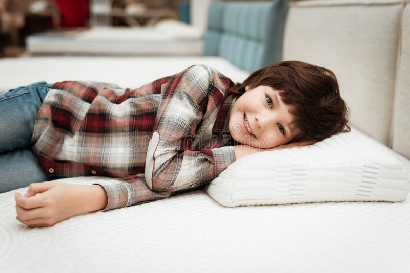 Joyful boy enjoying softness of orthopedic pillow rejoices in furniture store. Joyful little boy lies on orthopedic pillow in mattress store royalty free stock images