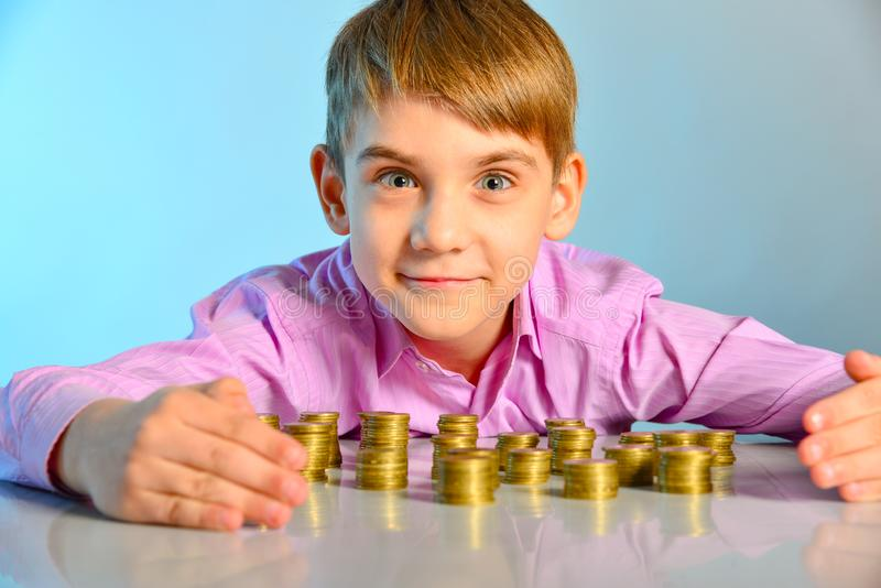 Joyful boy is guarding his cash savings. The concept of the economy of children`s business.  stock images
