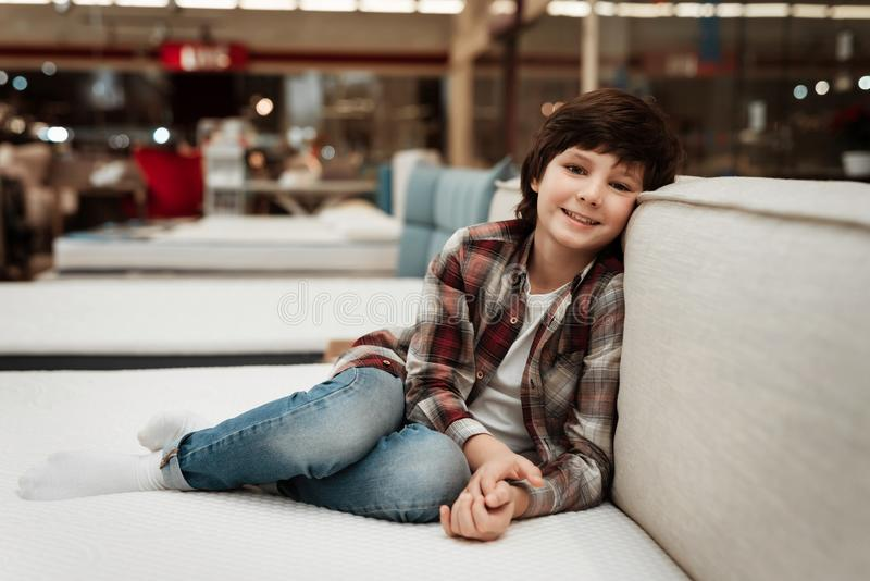 Joyful boy in store sits on bed in orthopedic mattress store. Check for softness of orthopedic furniture. Choosing mattress in store royalty free stock photo