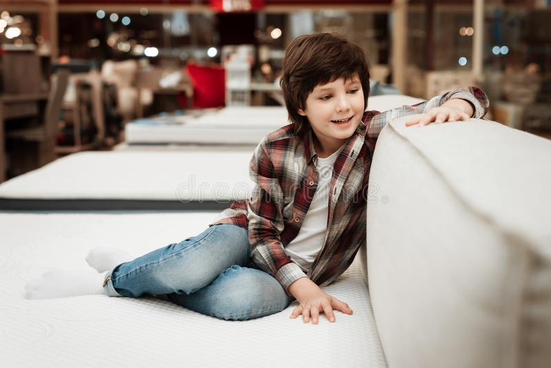Joyful boy in store sits on bed in orthopedic mattress store. Check for softness of orthopedic furniture. Choosing mattress in store royalty free stock image