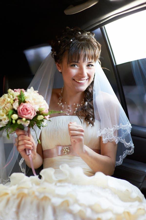 Joyful bride into limo stock image