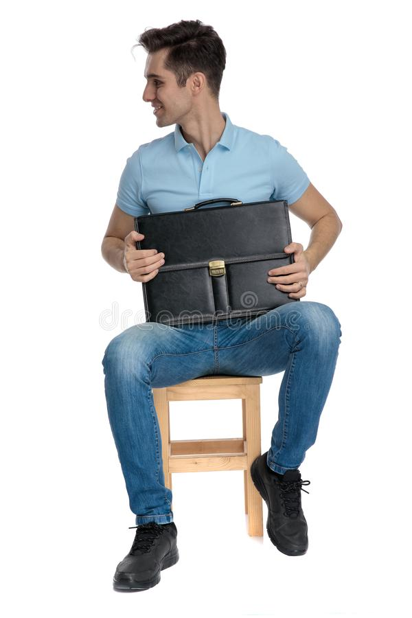 Joyful businessman looking to the side and holding his briefcase royalty free stock image