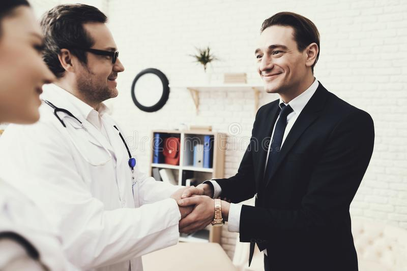 Joyful businessman shaking hands with doctor who cured ailment. Acknowledgments. Medical examination. Treatment of disease royalty free stock photography