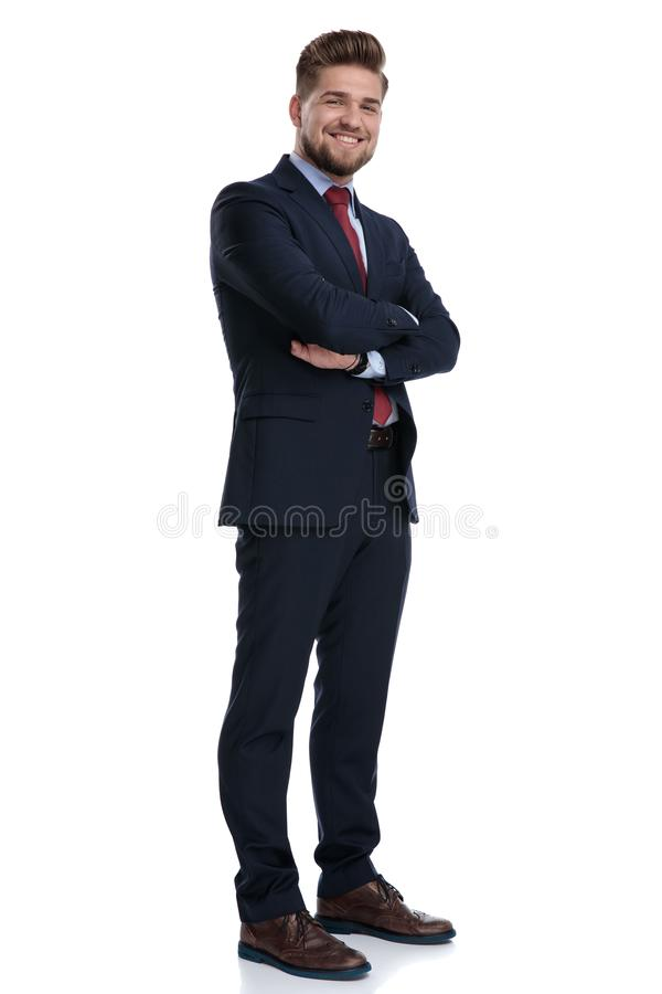 Joyful businessman standing with his arms folded and smiling. While wearing a blue suit and red tie, standing on white studio background royalty free stock photos