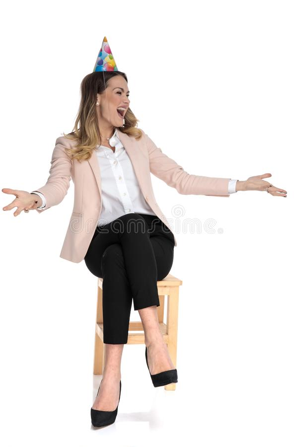 Joyful businesswoman with birthday hat looks up to side. While making inviting gesture and sitting on wooden chair on white background stock photo