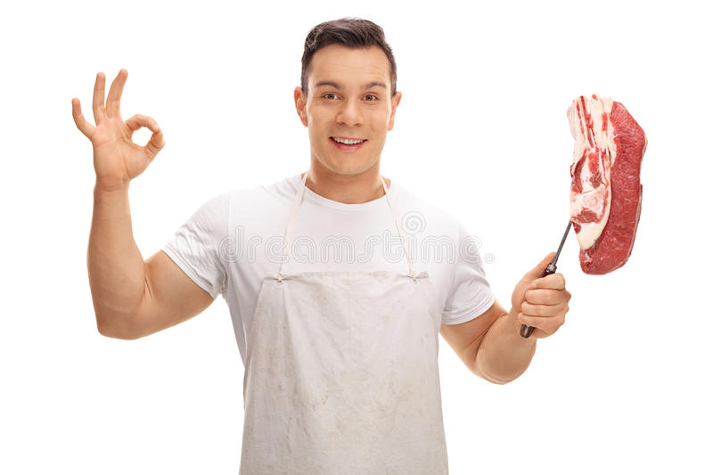 Joyful butcher making ok sign and holding fork with beef steak royalty free stock photography