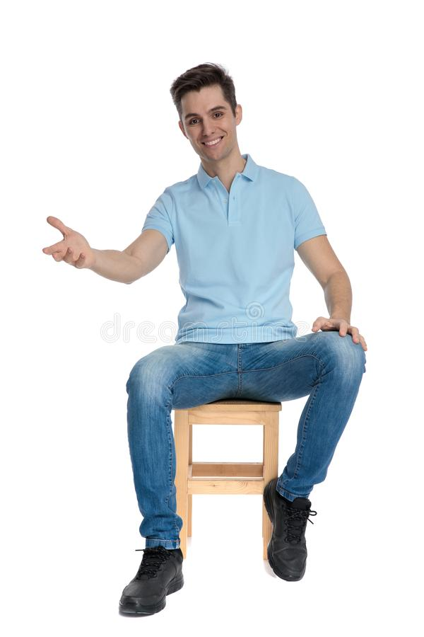 Joyful casual guy greeting and smiling. While wearing a blue shirt and jeans, sitting on a chair on white studio background stock image