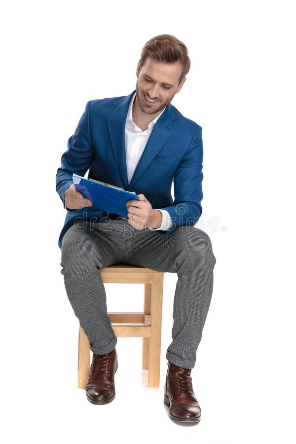Joyful casual guy laughing and reading from a clipboard. While sitting on a chair and wearing a suit on white studio background stock photo