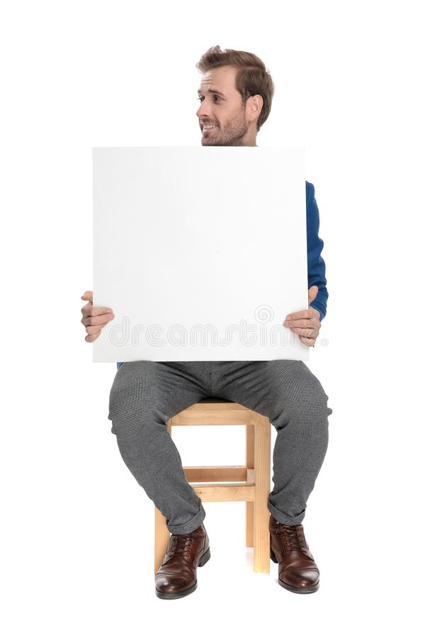 Joyful casual guy looking sideways and holding a billboard. While sitting on chair on white studio background royalty free stock photos