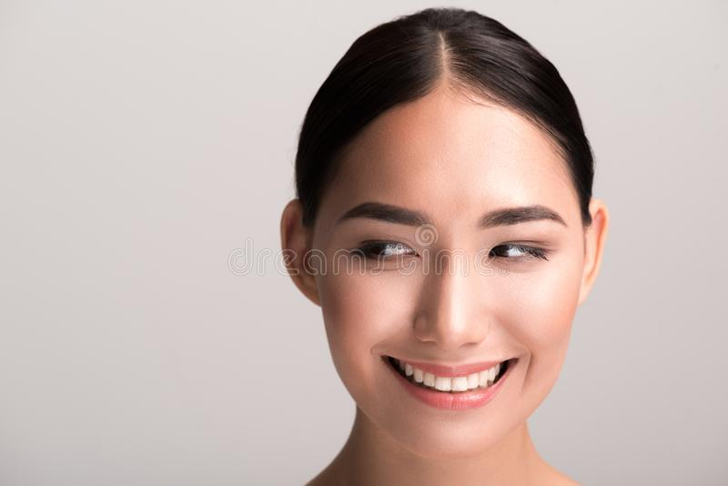 Joyful charming woman is enjoying her skincare. Feeling good. Close-up portrait of cheerful young asian girl with fresh and pure skin is looking aside playfully stock photography