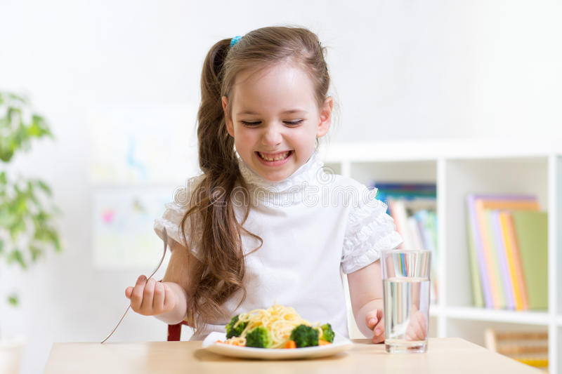 Joyful child eating healthy food at home. Joyful child girl eating healthy food at home or kindergarten royalty free stock photos