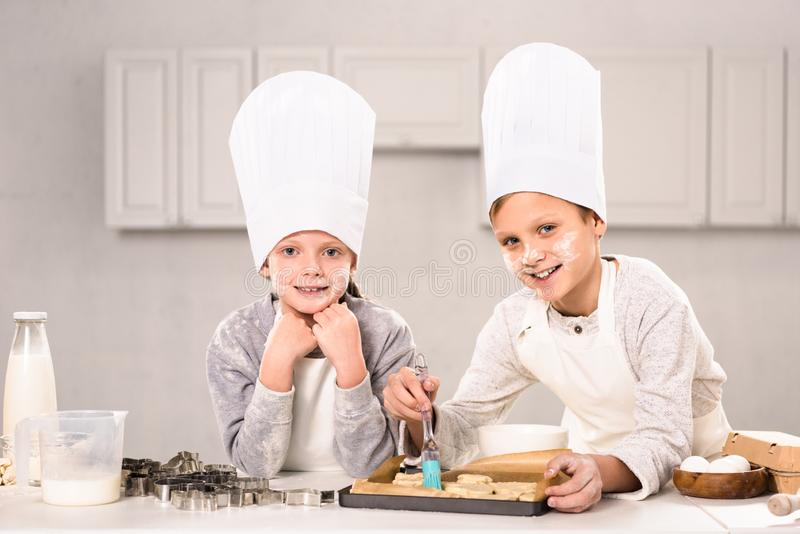 Joyful children in aprons brushing cookies on baking tray. In kitchen royalty free stock photos
