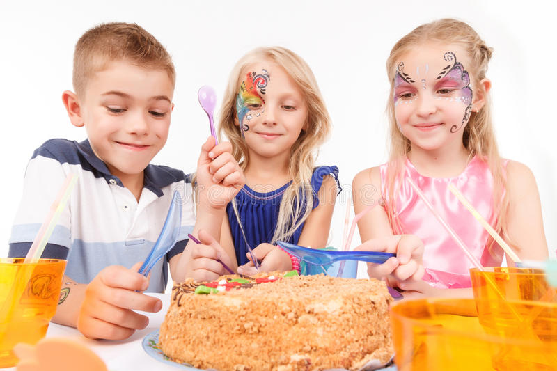 Joyful children eating birthday cake. Involved in birthday eating. Nice little children sitting at the table and waiting to taste festive cake royalty free stock photo