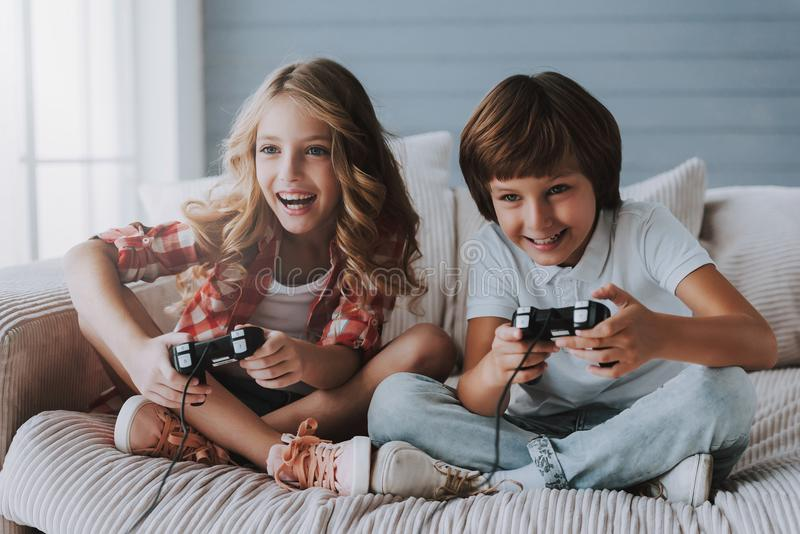 Joyful children with game controllers play video games at home. stock photo
