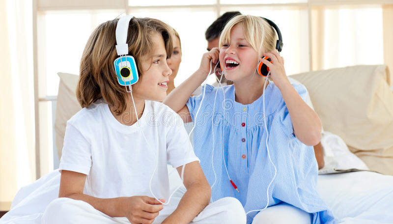 Joyful children having fun and listening music. At home royalty free stock photo