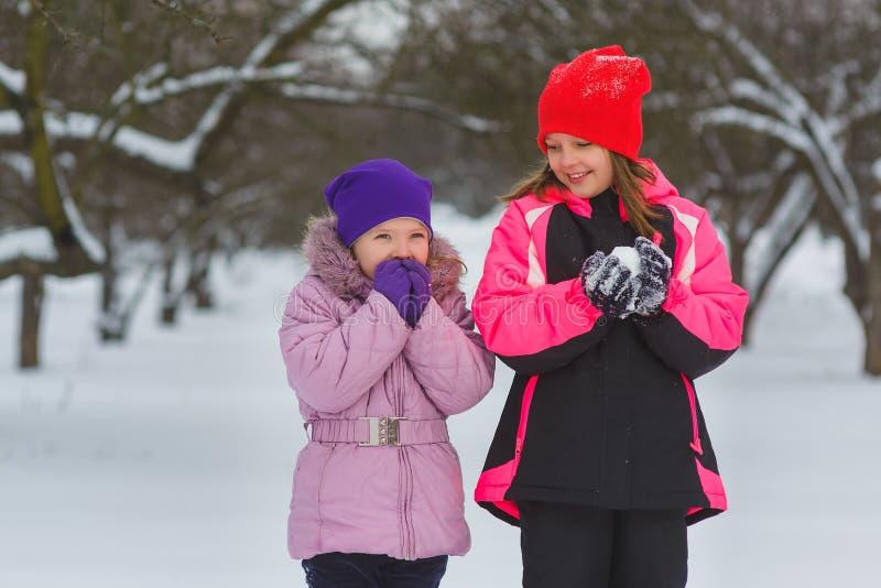 Joyful children playing in snow. Two happy girls having fun outside winter day stock photo