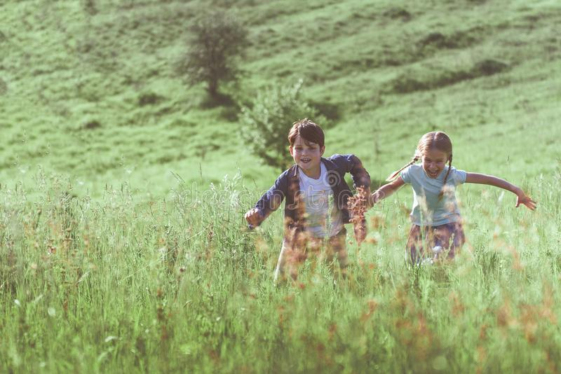Excited boy and girl shinning on grass royalty free stock photography