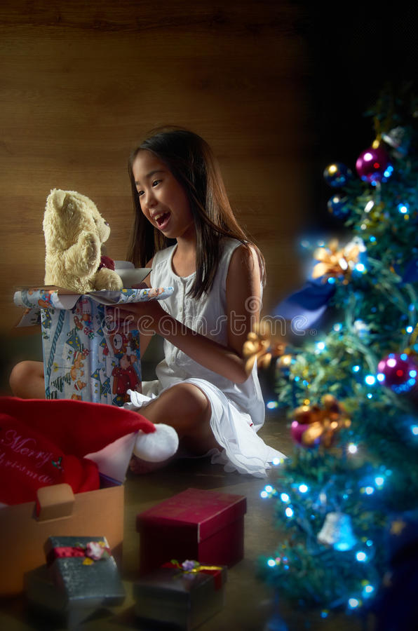 Joyful Christmas Present. Asian girl joyfully open up her christmas present