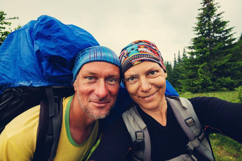 Joyful couple of adventurers taking selfie and having fun. On the green mountain slope during epic travel in the mountains stock photo
