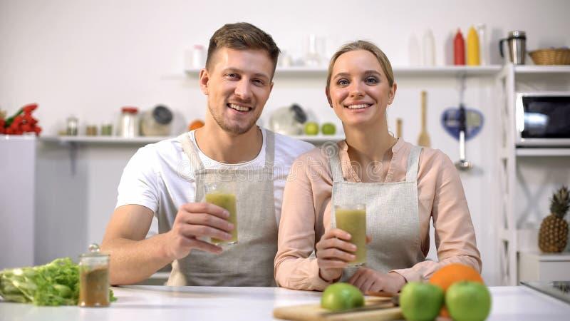 Joyful couple holding spirulina smoothie, recommending healthy drink, vitamins stock photo