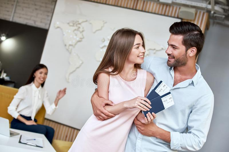 Joyful couple looking to each other and holding passport with flying tickets royalty free stock photography