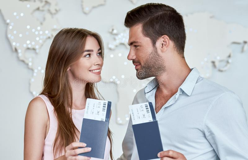 Joyful couple looking to each other and holding passport with flying tickets royalty free stock photos