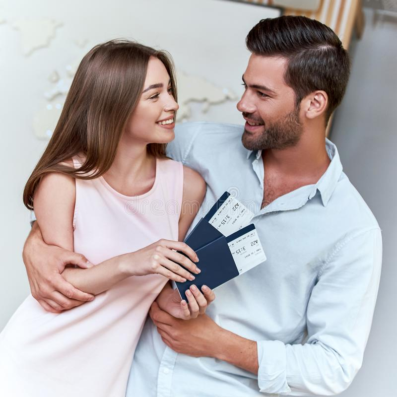 Joyful couple looking to each other and holding passport with flying tickets stock photo
