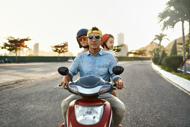 Parents with their little kid riding motorcycle on sunny city street royalty free stock images