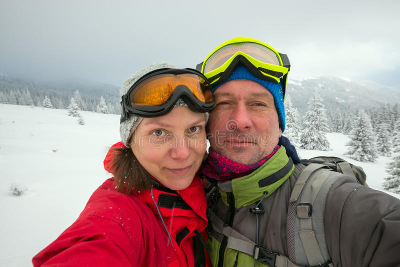 Joyful couple of travelers in goggles taking selfie. In the winter mountains after snow storm, happy winter adventure royalty free stock image