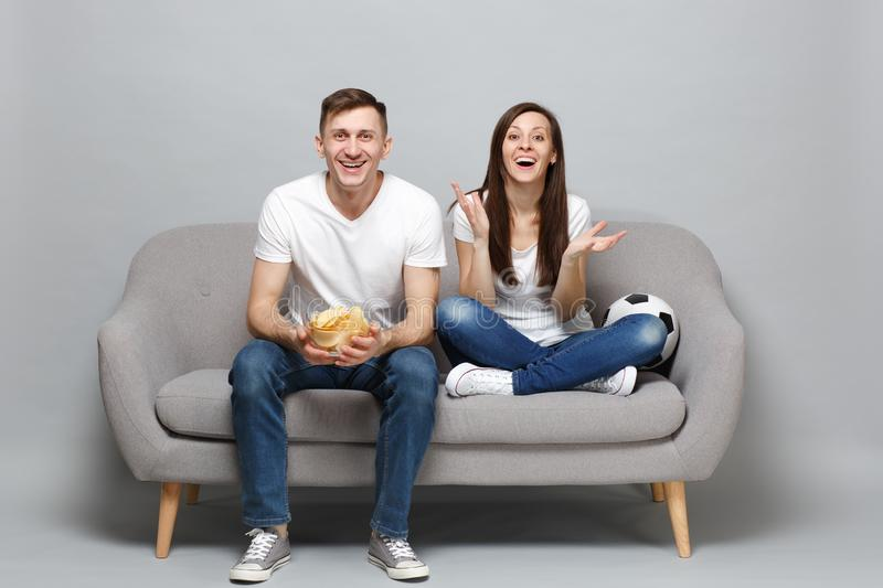 Joyful couple woman man football fans cheer up support favorite team with soccer ball, holding glass bowl of chips stock photo