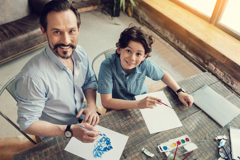 Joyful creative father and son painting together royalty free stock image