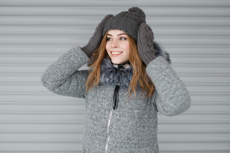 Joyful cute young woman in a gray knitted hat in a stylish gray coat with fur in knitted vintage mittens with a beautiful smile. Near the metal white wall royalty free stock image