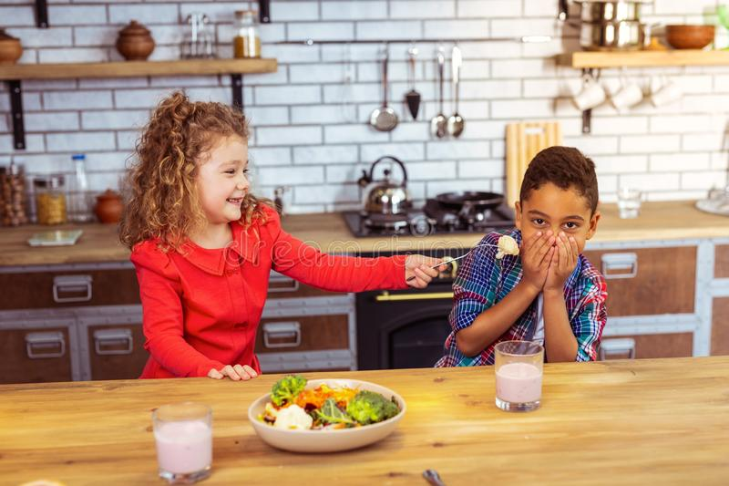 Joyful dark-skinned boy putting hands on his mouth. Do not like it. Playful blonde girl expressing positivity while trying to feed her cousin stock image