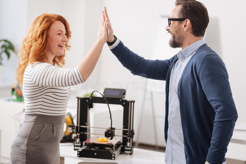 Joyful delighted colleagues giving each other high five. Great job. Joyful delighted happy colleagues looking at each other and giving a high five while stock image