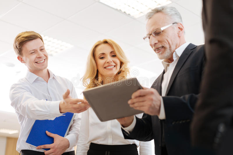 Joyful delighted colleagues looking at the tablet screen. Modern device. Joyful delighted positive colleagues smiling and looking at the tablet screen while stock image