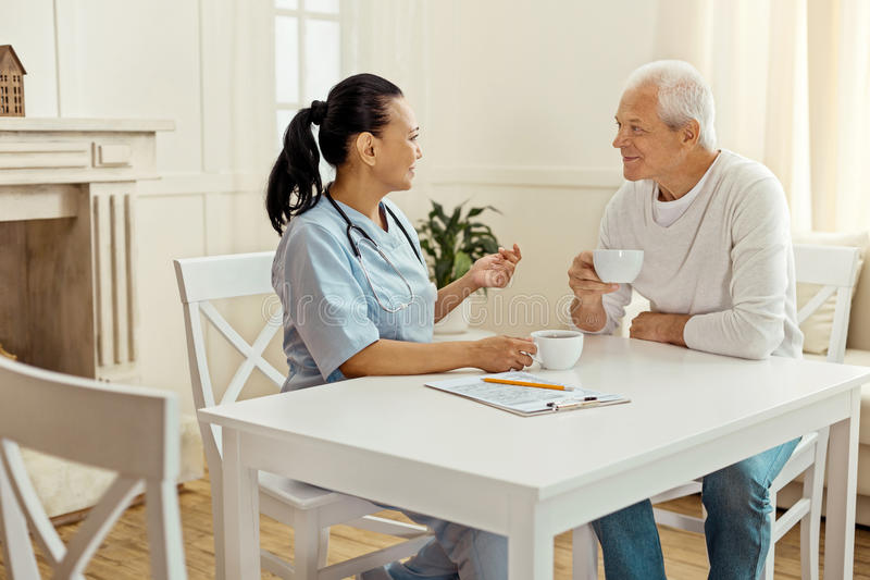 Joyful delighted man listening to his caregiver. Interesting story. Joyful delighted aged men smiling and listening to his caregiver while having tea with her stock photo
