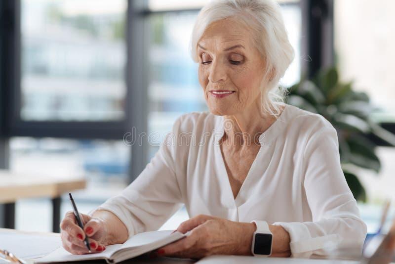 Joyful delighted woman writing memoirs stock image