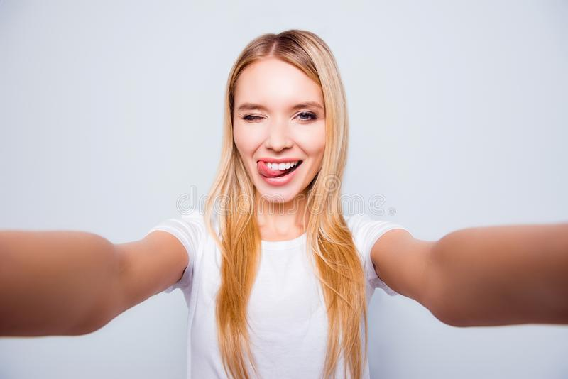 Joyful delightful happy excited attractive young blonde is giving a wink and taking a selfie, isolated on grey background royalty free stock photos