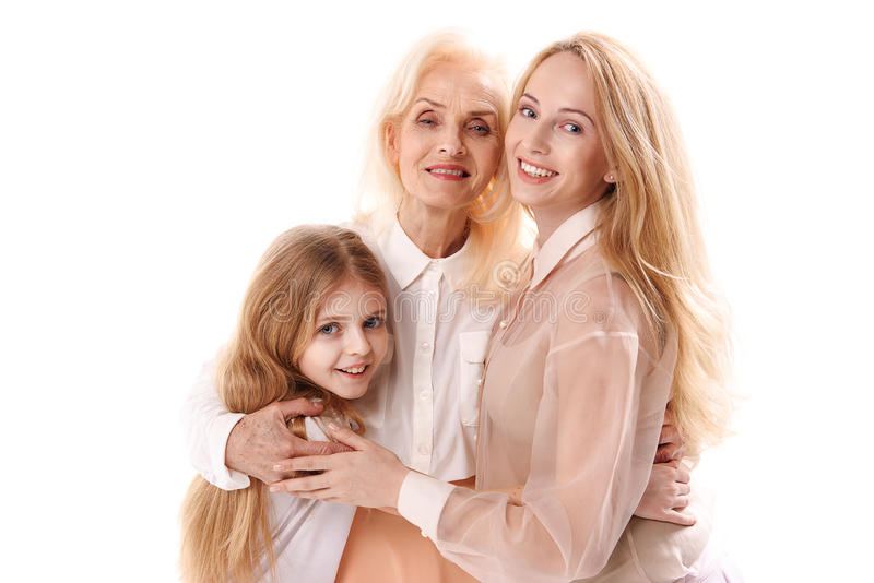 Joyful different aged female persons. What love is. Granddaughter is hugging her mother and granny. They are looking at camera with happiness in their eyes royalty free stock photography