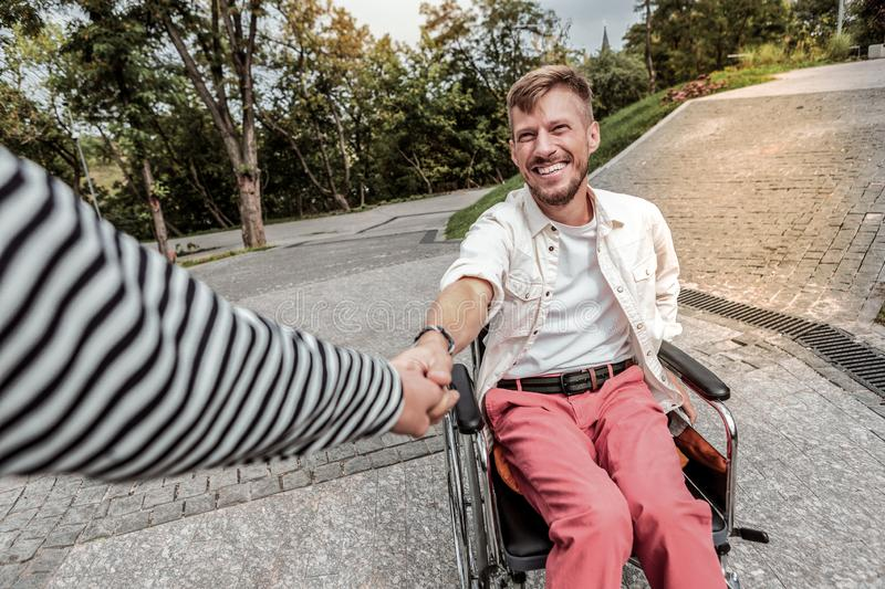 Joyful disabled male person following his friend. My gladness. Kind men expressing positivity while laughing at funny joke stock photo