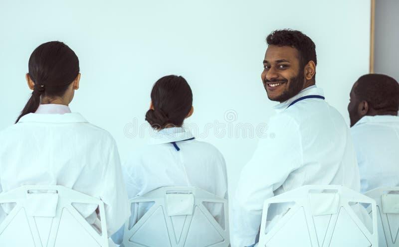 Joyful dokter zit met collega's voor de witte muur stock fotografie