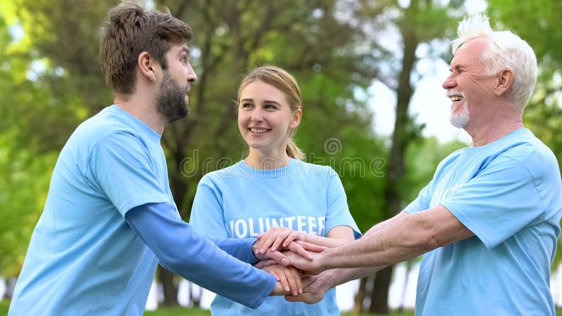 Joyful eco volunteers putting hands together, teamwork cooperation gesture. Stock photo royalty free stock photos