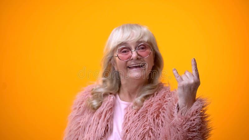 Joyful elderly lady in funny pink clothes making rocker gesture, positiveness royalty free stock photo