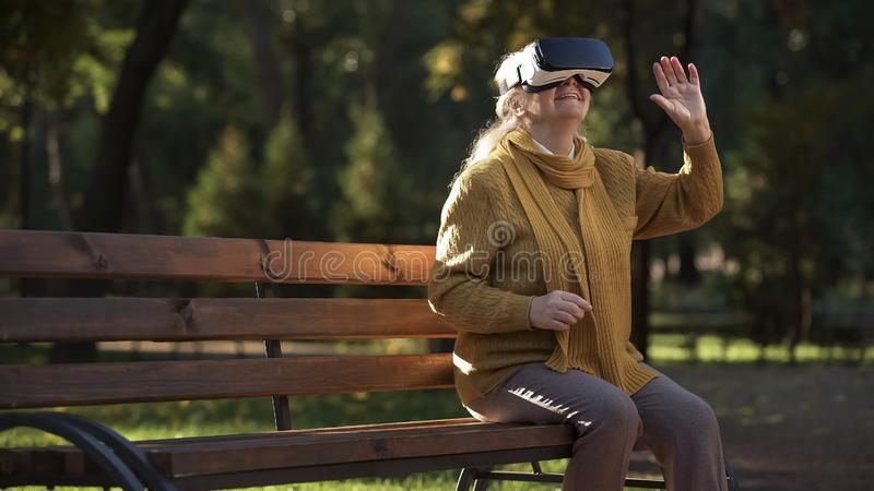 Joyful elderly lady using vr headset sitting on bench in park, entertainment stock photo