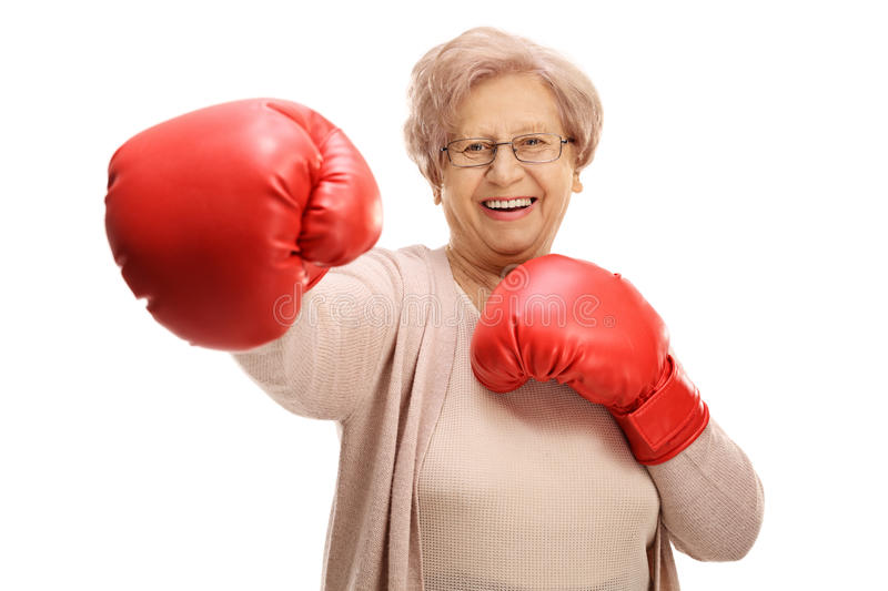Joyful elderly woman with boxing gloves throwing a punch royalty free stock images