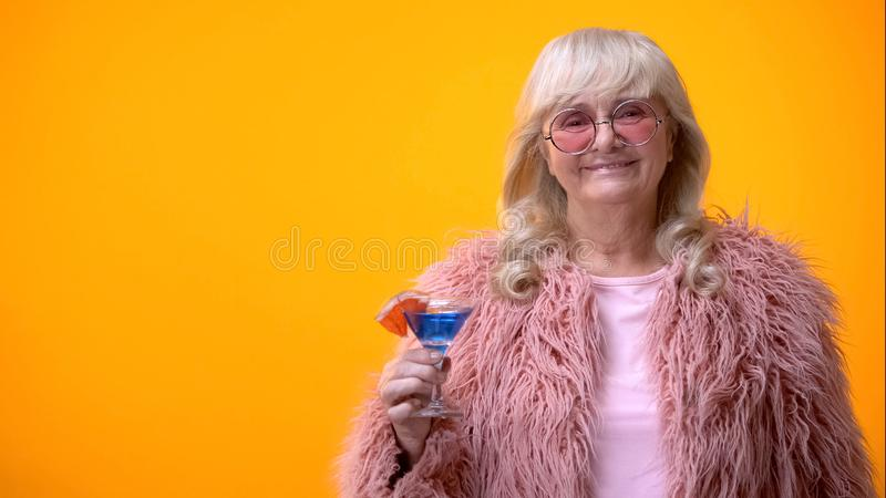 Joyful elderly woman holding blue cocktail, smiling into camera, party mood stock photos