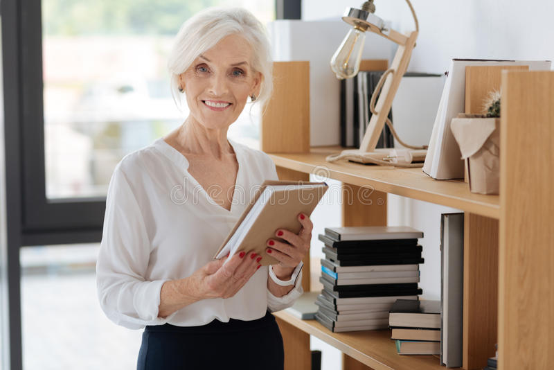 Joyful elderly woman holding a book royalty free stock image