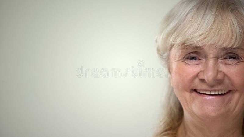 Joyful elderly woman smiling on camera, positive life attitude, secured old age stock images